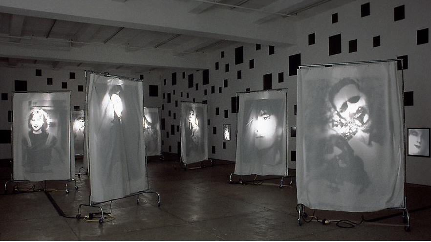 Christian Boltanski, Reflection, 2000, 400 black mirrors, 9 wheeled racks with suspended transparencies on cloth sheets.