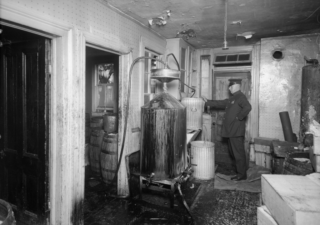 A police officer inspecting stills for bootleg liquor in Brooklyn (July 1927) (courtesy New York City Municipal Archives)