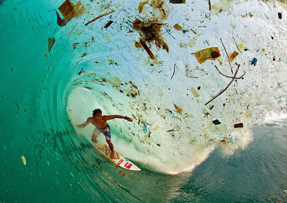 A surfer riding a wave of rubbish near Java in Indonesia, the world's most populous island.
