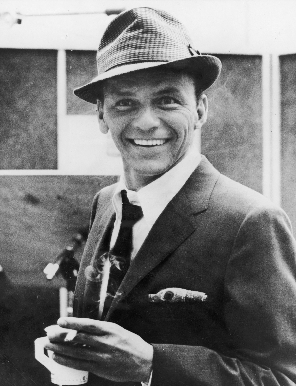 American singer and actor Frank Sinatra (1915 - 1998) smiles while holding a cigarette and a cup of coffee in a recording studio, 1950s. (Photo by Hulton Archive/Getty Images)