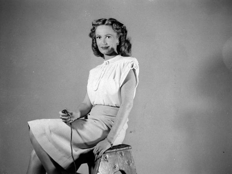 Actress Geraldine Fitzgerald holding shutter release as she takes her own photograph.