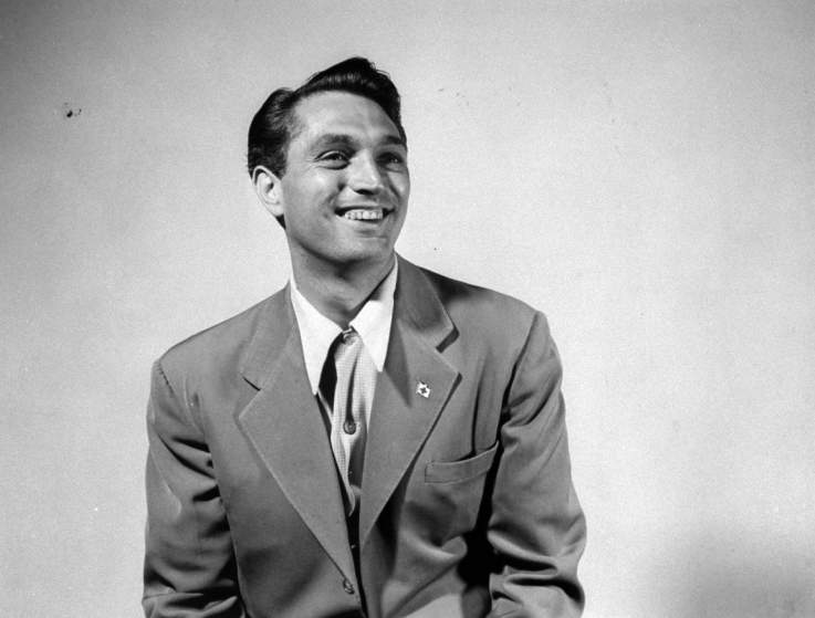 Actor Robert Alda posing as he takes his own photograph.