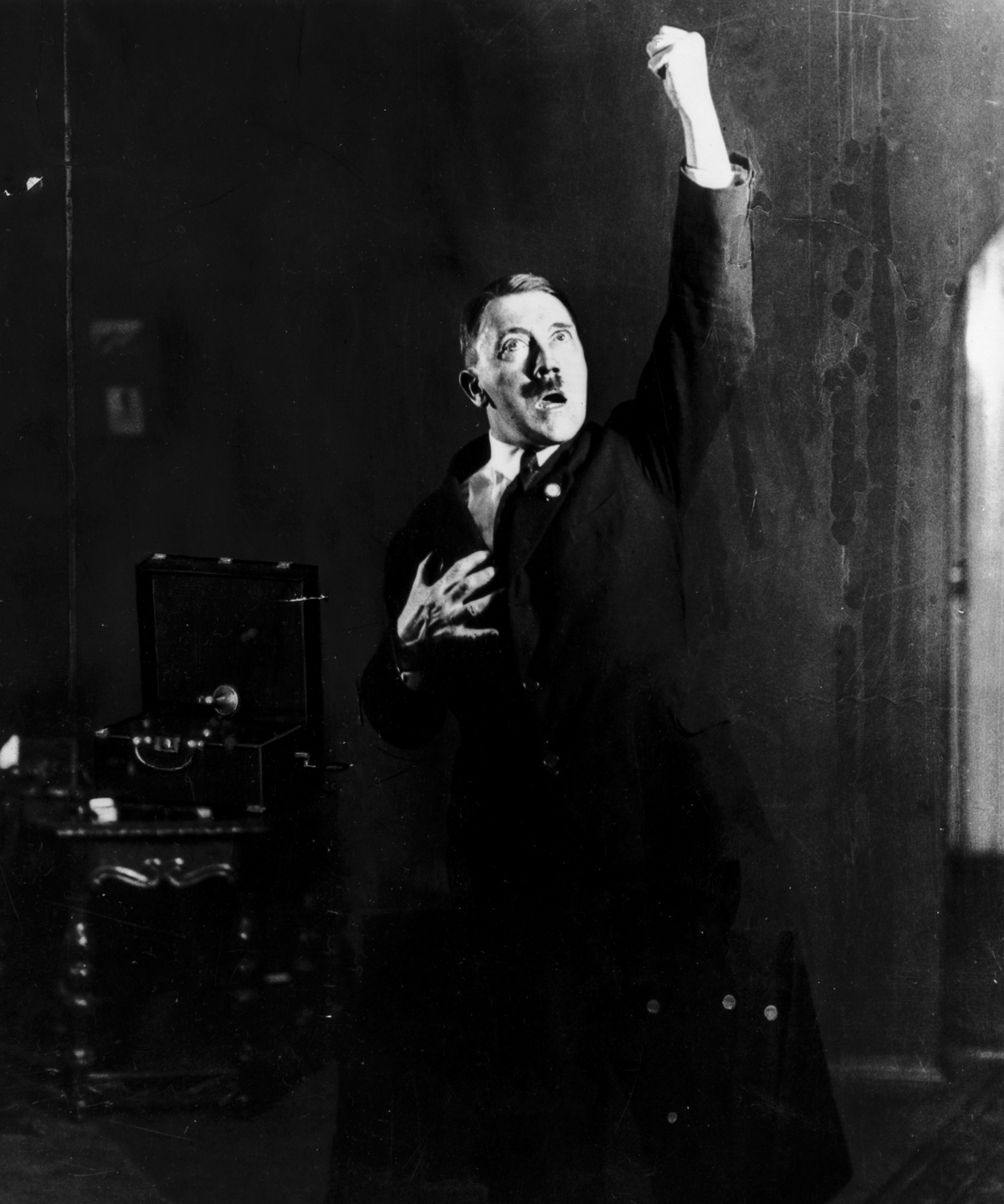 Adolf Hitler (1889 - 1945), leader of the National Socialist German Workers' Party (NSDAP), strikes a pose for photographer Heinrich Hoffmann whilst listening to a recording of his own speeches. After seeing the photographs, Hitler ordered Hoffmann to destroy the negatives, but he disobeyed. (Photo by Heinrich Hoffmann/Getty Images)