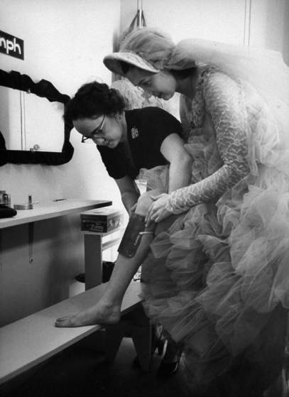 The bride Mary Beth Sanger, getting metal weights on knee to hold her under.